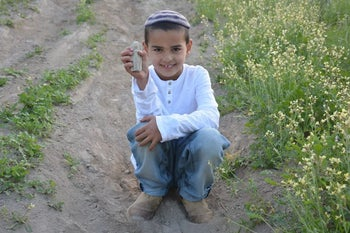 Ori Greenhut, 7, wearign a skullcap, white shirt and jeans, holding the Canaanite figurine he found at Tel Rehov while on a trip with friends.