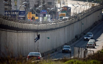 A Palestinian man climbs over a section of the separation barrier between A-Ram in the West Bank and East Jerusalem, February 24, 2016.