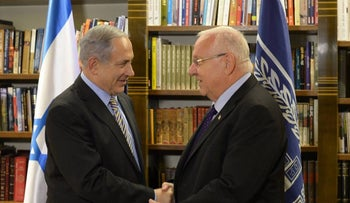 A file photo of Netanyahu and Rivlin shaking hands.