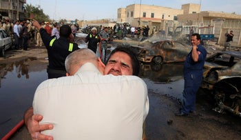 An Iraqi man is comforted at the scene of a car bomb attack in Baghdad, Iraq, Friday, March 29, 2013.