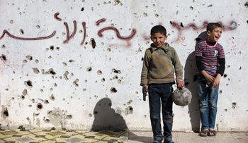 "A Syrian boy holds a toy gun as he plays soccer with others between destroyed buildings with graffiti that reads ""Syria al-Assad,"" in the old city of Homs, Feb. 26, 2016."