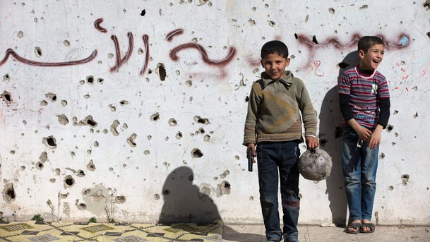 """A Syrian boy holds a toy gun as he plays soccer with others between destroyed buildings with graffiti that reads """"Syria al-Assad,"""" in the old city of Homs, Feb. 26, 2016."""