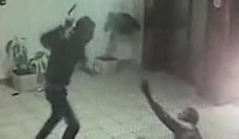 A screenshot from security footage showing the assailant coming at the security guard with an ax.