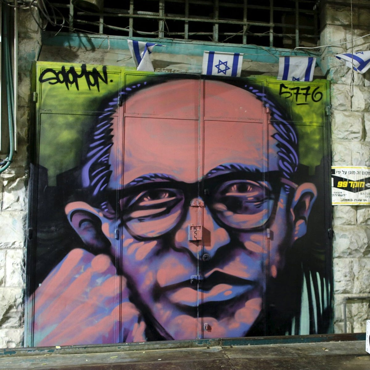 A spray-painted portrait is seen on the metal shutter of a closed storefront in Mahane Yehuda, one of Jerusalem's most popular outdoor markets February 24, 2016. Picture taken February 24, 2016.