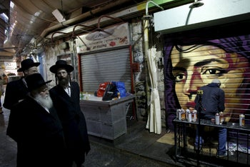 Ultra-Orthodox Jewish men (L) walk past artist Solomon Souza, 22, as he spray-paints a portrait on the metal shutter of a closed storefront in Mahane Yehuda, one of Jerusalem's most popular outdoor markets February 24, 2016. Picture taken February 24, 2016.
