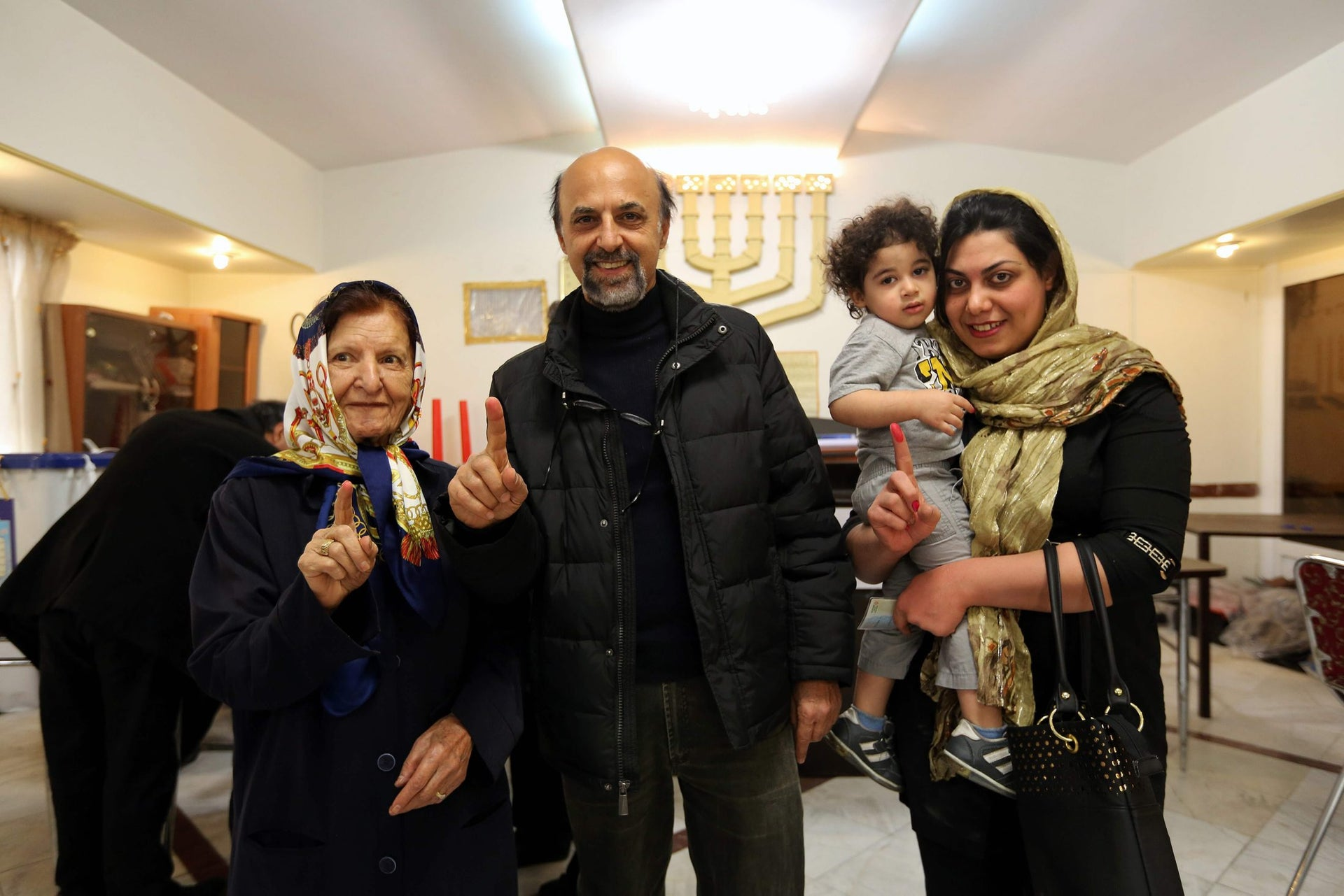 A Jewish Iranian family displays their ink-stained fingers after casting their vote at a synagogue used as a polling station for the Jewish community in Tehran on February 26, 2016.