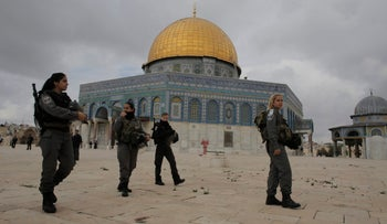 Israeli border police officers walk in front of the Dome of the Rock on the Temple Mount, Jerusalem.