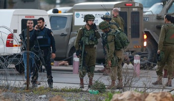 Israeli security forces monitor the area where a Palestinian man tried to stab Israeli soldiers before being shot dead at a checkpoint near Ramallah, in the West Bank, on February 26, 2016.