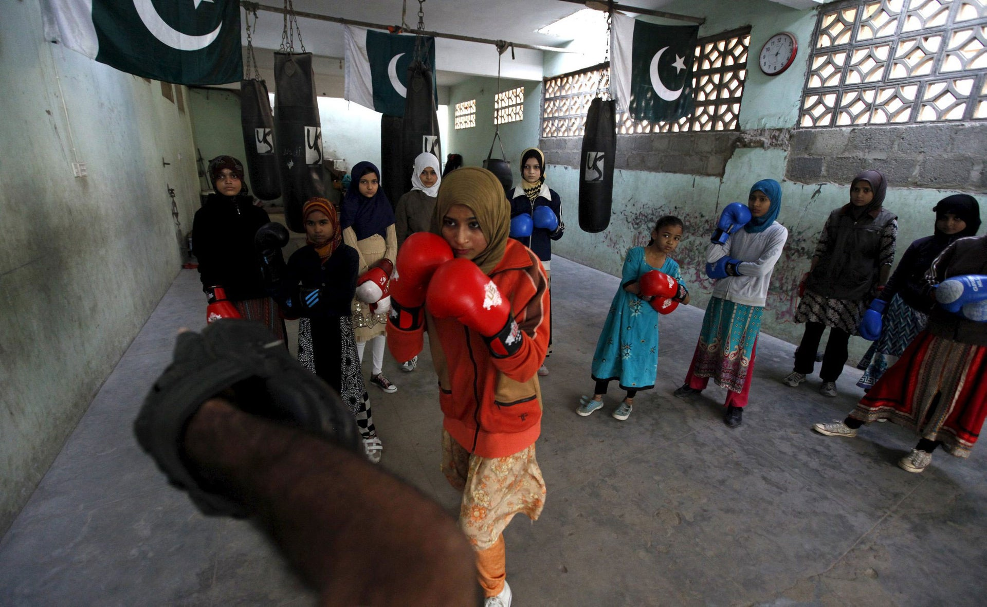 Anum, 17, punches padding with coach Younus Qambrani during an exercise session at the first women's boxing camp in Karachi, Pakistan, February 20, 2016.