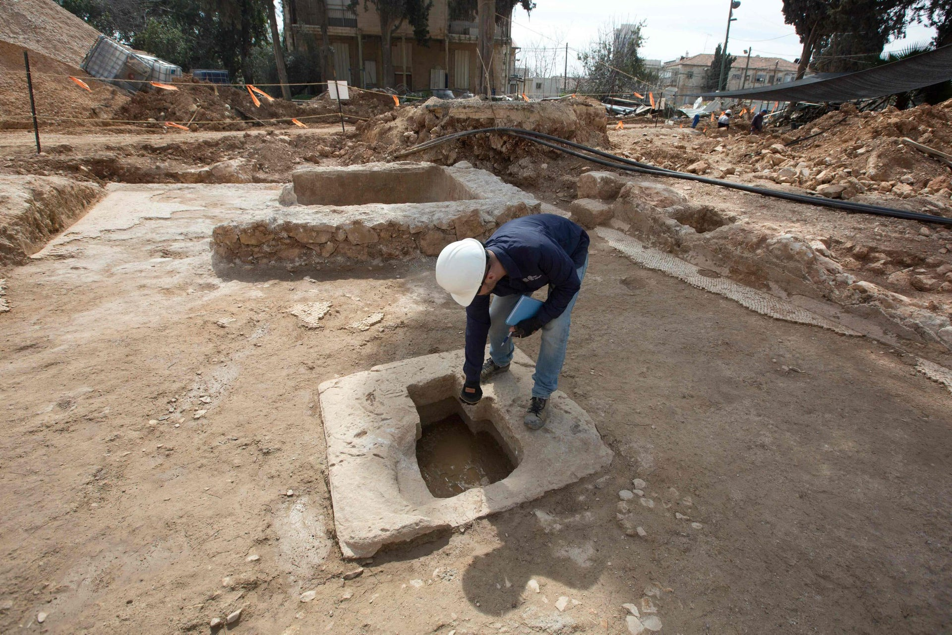 A worker with the Israeli Antiquities Authority works at the site where a large roman winery was found in Jerusalem's Schneller Compound, in the heart of construction site for new residential houses, on March 2, 2016.