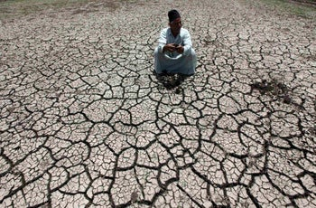 An Egyptian farmer squats on cracked soil of a farm previously irrigated by the Nile river, June 5, 2013.