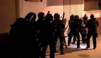 Spanish police prepare to enter a building during an operation in Spain's northern African enclave of Ceuta, in this still image from video released February 23, 2016.