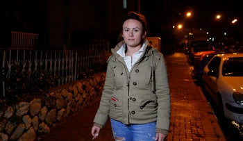 Katy Krakolov. A young woman wearing fashionably ripped jeans and a casual jacket and holding a cigarette.