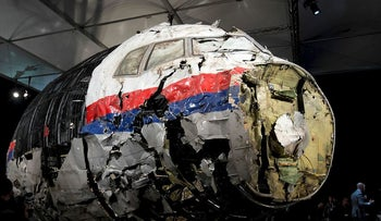 In this Tuesday, Oct. 13, 2015 file photo, the reconstructed wreckage of Malaysia Airlines Flight MH17 is put on display during a press conference