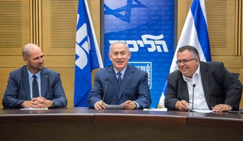 Prime Minister Benjamin Netanyahu (center), flanked by Amir Ohana (left) and David Bitan, at a Likud faction meeting, July 10, 2017.