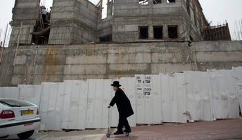 An ultra Orthodox Jewish youth rides a push scooter past a building under construction in Ramat Shlomo, a Jewish settlement in the mainly Palestinian eastern sector of Jerusalem, on June 5, 2014.