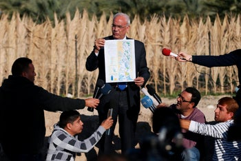 FILE PHOTO: Palestinian Chief negotiator Saeb Erekat holds a map as he speaks to media about the Israeli plan to appropriate land, in Jordan Valley near the West Bank city of Jericho, January 20, 2016.
