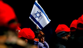 An archive picture of a woman holding an Israeli flag outside the Israeli consulate in New York.