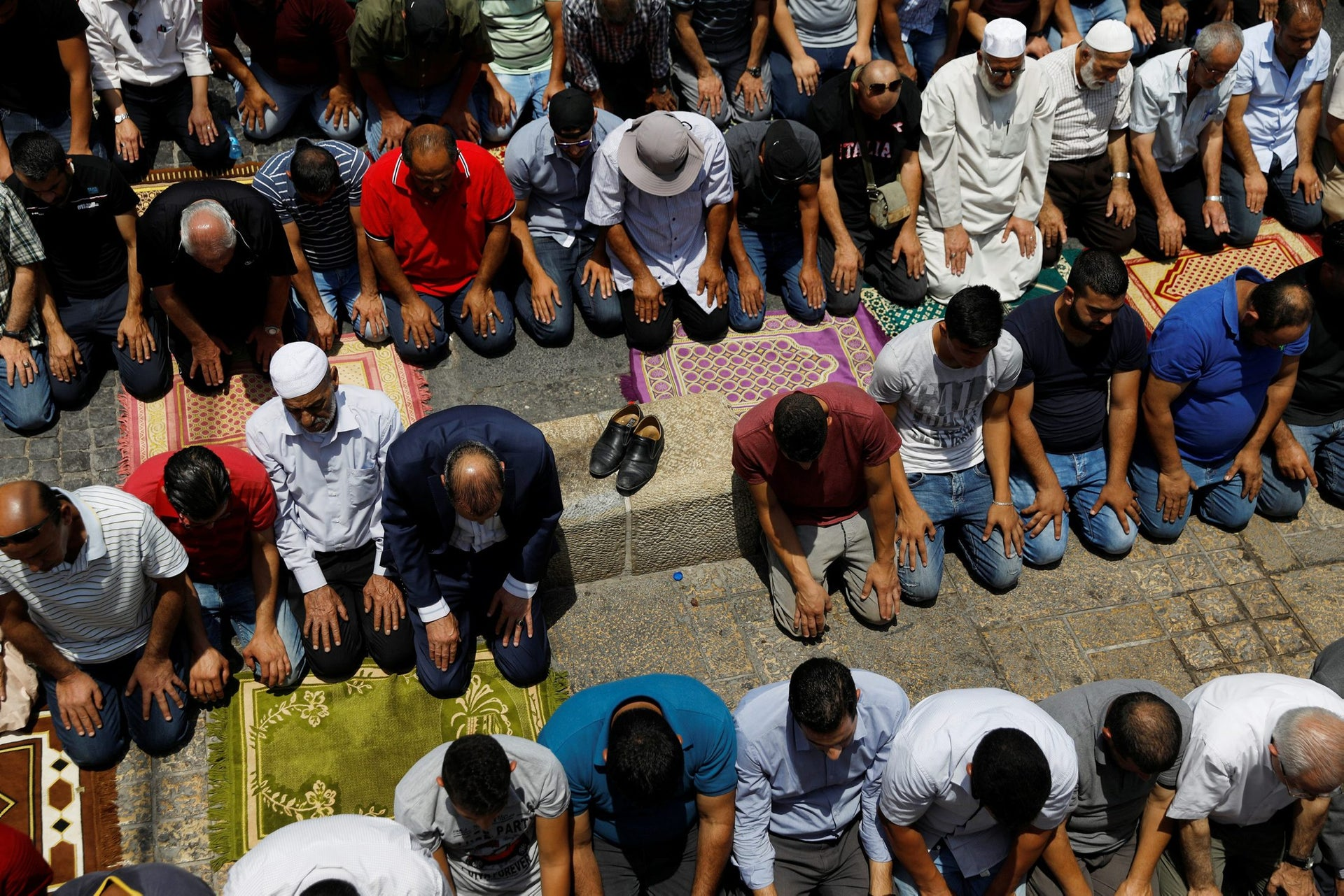 Palestinians pray at Lions' Gate, an entrance to Jerusalem's Old City, in protest over Israel's new security measures at the compound housing al-Aqsa mosque.
