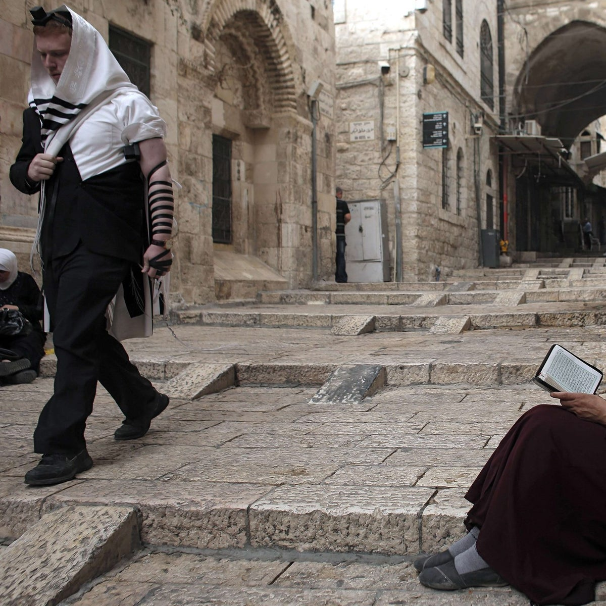 A Palestinian woman reads a copy of the Koran, Islam's holy book, as a Jewish Orthodox man walks past her in Jerusalem's Old City on September 10, 2015.