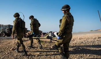 Israeli soldiers evacuating a wounded Syria rebel from the border area.