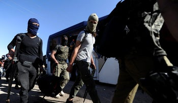 Rebel fighters carry their weapons and belongings, evacuating besieged Waer district in Homs, Syria on May 21, 2017 after an agreement was reached between government forces and rebels.