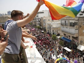 A man waves a flag as the Gay Pride Parade passes in the streets of Tel Aviv on June 3, 2016.