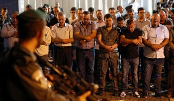 Israeli security forces stand guard in front of Muslim worshippers praying outside a main entrance to the Al-Aqsa Mosque compound in Jerusalem's Old City, July 19, 2017.
