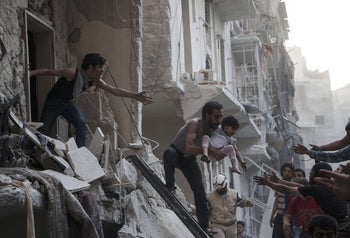 A man evacuates a child from a building following a reported barrel bomb attack by Syrian government forces on the northern Syrian city of Aleppo. May 30, 2015