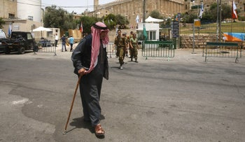 A Palestinian man walks past the closed off area outside the Tomb of the Patriarchs, also known as the Ibrahimi Mosque, in Hebron, July 12, 2017.