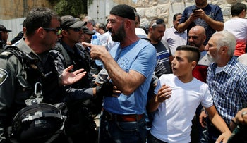 Israeli security forces argue with a Palestinian near the Temple Mount in Jerusalem, July 17, 2017.