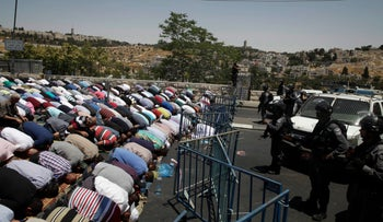 Palestinian Muslim worshippers prevented from entering the Al-Aqsa Mosque pray outside Jerusalem's Old City, Friday, July 14, 2017.