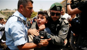A Palestinian youth is detained by an Israeli border police officer during scuffles that erupted after Palestinians held prayers in Jerusalem protest over the Temple Mount metal detectors July 17, 2017.