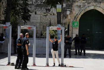A woman checks metal detectors as they are installed at an entrance to the compound known to Muslims as Noble Sanctuary and to Jews as Temple Mount, in Jerusalem's Old City July 16, 2017
