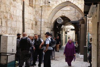 A Muslim woman walks past Israel Police officer in Jerusalem's Old City ahead of Friday prayers, July 21, 2017