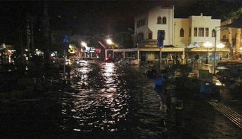 People walk at a flooded coastal road after an earthquake on the Greek island of Kos, July 21, 2017.