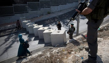 Israeli Border Police checking the ID of a Palestinian woman next to newly placed concrete blocks in an East Jerusalem neighborhood, October 2015.