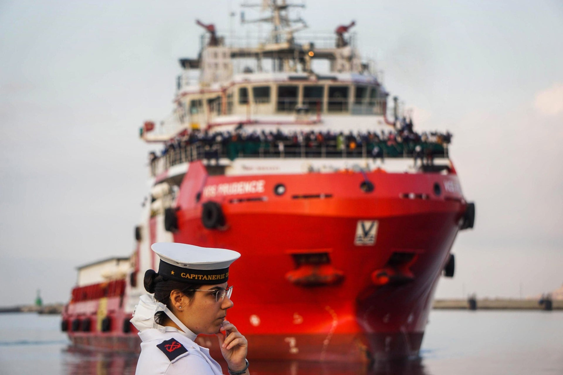 An Italian Coast Guard waiting as the Vos Prudence ship, carrying more than 900 migrants rescued at sea, comes in to dock at Salerno's harbor, Italy.