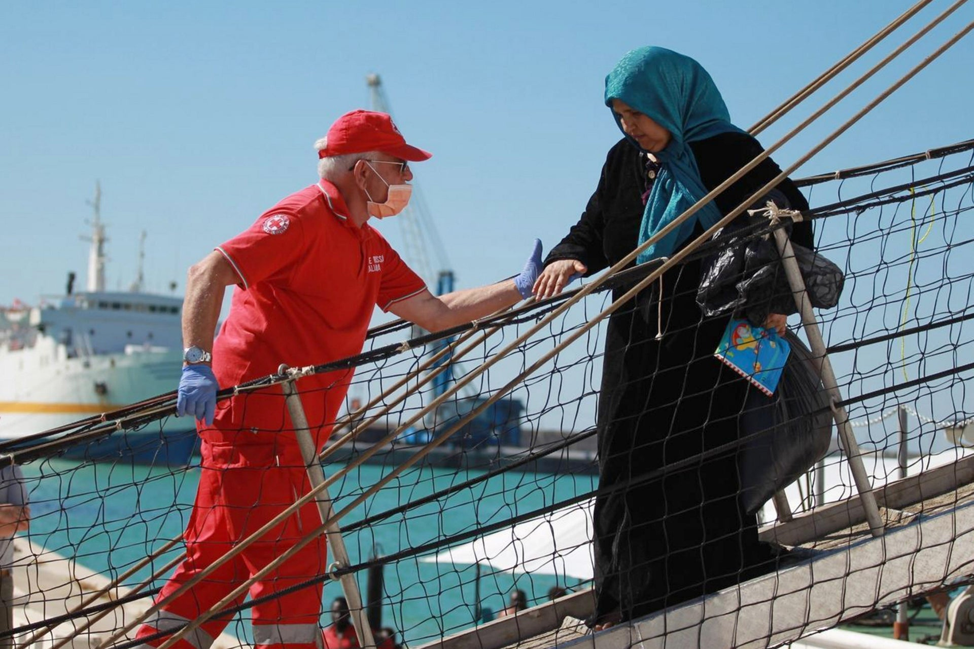 A migrant woman being helped from a Spanish NGO ship at the Sicilian port of Porto Empedocle, southern Italy, in July.