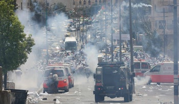 Tear gas fumes billow as Palestinian protesters flee during clashes with Israeli forces after Friday prayers at the main entrance of the West bank city of Bethlehem on July 21, 2017.