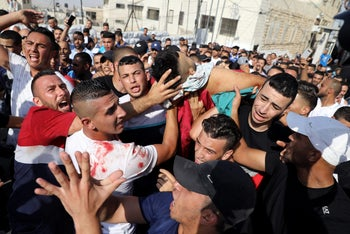 Mourners carry the body of Mohammad Abu Ghannam during his funeral in the East Jerusalem neighborhood of A-Tur, July 21, 2017.