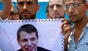 Supporters hold a photo of exiled former Gaza strongman Mohammed Dahlan during a protest against metal detectors that Israel has installed at the Al-Aqsa Mosque compound in Jerusalem, in Gaza City