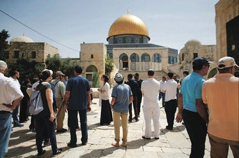 Israeli police accompany Jewish visitors past the Dome of the Rock during a visit to the Temple Mount in the Old City of Jerusalem, April 25, 2016.