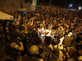 Israeli security forces stand by as Palestinian Muslim worshippers pray outside Lions' Gate, a main entrance to the Al-Aqsa mosque compound in Jerusalem's Old City, on July 23, 2017, in protest against new Israeli security measures