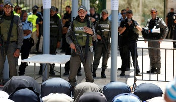 Palestinians pray in front of Israeli policemen and newly installed metal detectors at an entrance to the Temple Mount in Jerusalem's Old City, July 16, 2017.