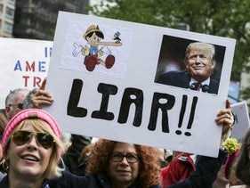 """A demonstrator holds a sign during the """"March For Truth"""" protest at Foley Square in New York."""