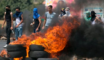 Palestinian protesters burn tires during a demonstration at the Hawara checkpoint, south of Nablus in the Israeli-occupied West Bank, on July 21, 2017 against the Israeli security measures implemented at Al-Aqsa mosque compound.
