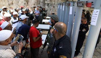 Muslim worshipers stand in front of Israeli policemen and newly installed metal detectors at an entrance to the compound known to Muslims as Noble Sanctuary and to Jews as Temple Mount, in Jerusalem's Old City July 16, 2017.
