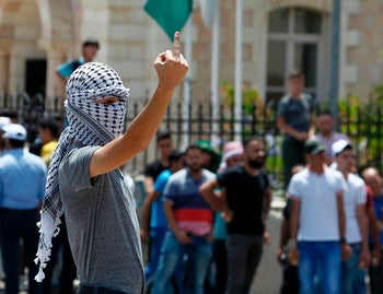 A Palestinian protester flashes his middle finger towards Israeli soldiers during clashes after Friday prayers at the main entrance of the West bank city of Bethlehem on July 21, 2017 at a protest against new Israeli security measures implemented at Al-Aqsa mosque complex, known to Jews as the Temple Mount, in Jerusalem.
