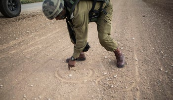A Bedouin soldier examines the ground for markings at the border of Israel and the Gaza Strip May 19, 2014 in Nahal Oz.
